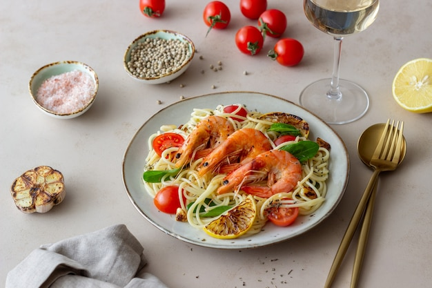 Pasta spaghetti mit garnelen, tomaten, knoblauch, spinat und zitrone. italienische küche. meeresfrüchte. diät. Premium Fotos