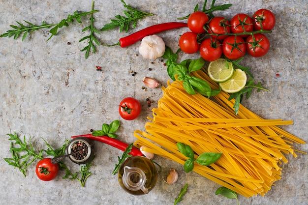 Pasta tagliatelle und zutaten zum kochen (tomaten, knoblauch, basilikum, chili). ansicht von oben Kostenlose Fotos
