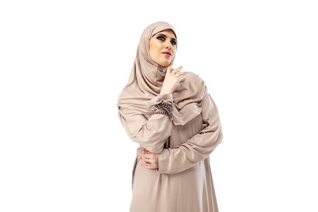 Pastell. schöne arabische frau, die im isolierten mode-, schönheits-, stilkonzept des stilvollen hijab aufwirft. weibliches model mit trendigem make-up, maniküre und accessoires. Kostenlose Fotos