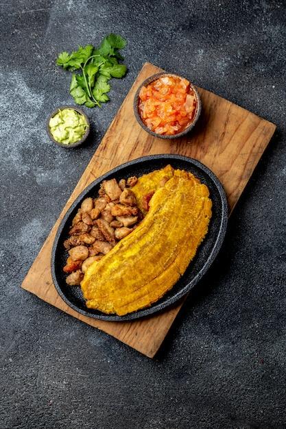 Patacon oder toston, gebratene und abgeflachte ganze grüne bananenbanane auf weißer platte mit tomatensauce und chicharron Premium Fotos