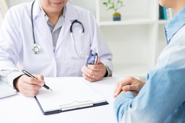 Patient, der aufmerksam auf einen männlichen arzt hört, der patientensymptome erklärt oder eine frage stellt, während sie in einer konsultation den papierkram besprechen Premium Fotos