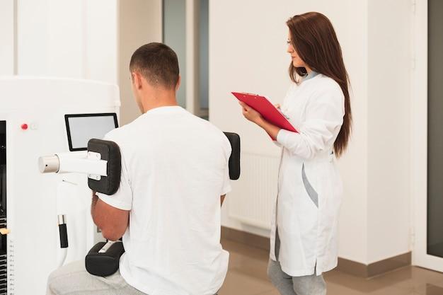 Patient der hinteren ansicht, der das medizinische gerät überwacht vom doktor verwendet Kostenlose Fotos