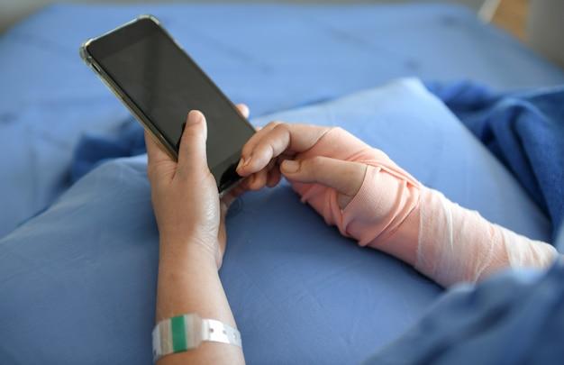 Patient trägt eine schiene im arm. er spielt smartphone. Premium Fotos