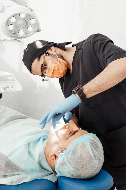 Patient und zahnarzt während der implantatinsertion. echte bedienung. zahnextraktion, implantate. berufsuniform und ausrüstung eines zahnarztes. gesundheitswesen ausstattung eines arztarbeitsplatzes. zahnheilkunde Premium Fotos