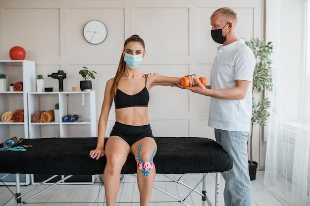 Patientin bei physiotherapie mit mann und hantel Kostenlose Fotos