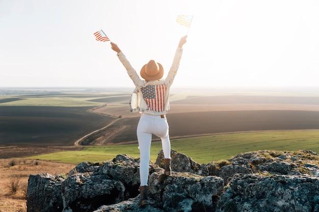 Patriotische frau, die mit amerikanischen flaggen auf berg aufwirft Kostenlose Fotos