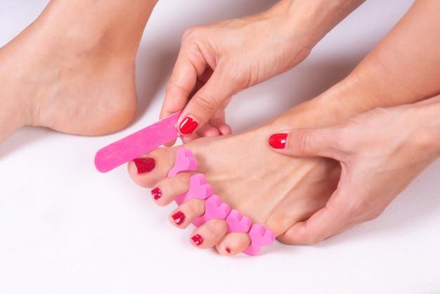 Pediküre auf die füße der frau mit roten zehennägeln auftragen, in rosafarbenen zehentrennern. Premium Fotos
