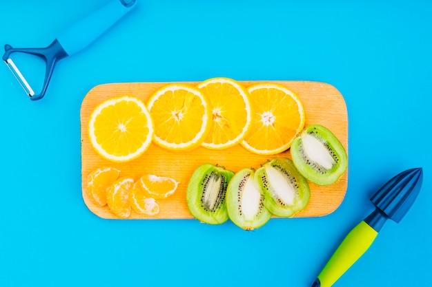 Peeler und hand juicer mit orangen und kiwischeiben auf schneidebrett gegen blauen hintergrund Kostenlose Fotos