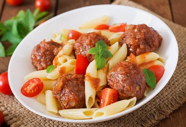 Penne pasta mit fleischbällchen in tomatensauce in einer weißen schüssel Kostenlose Fotos