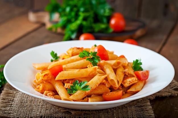 Penne-teigwaren in der tomatensauce mit huhn und tomaten auf einem holztisch Premium Fotos