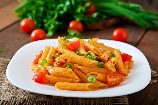 Penne-teigwaren in der tomatensauce mit huhn und tomaten auf einem holztisch Kostenlose Fotos