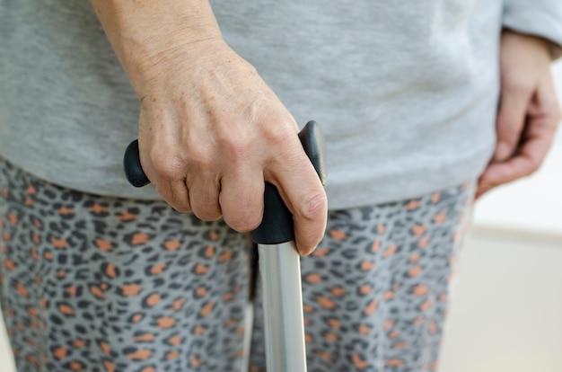 Pensionierte frau mit metall spazierstock in der hand zu hause halten Premium Fotos