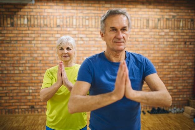 Pensionierte paare, die in der turnhalle meditieren Kostenlose Fotos
