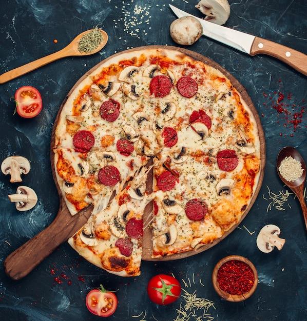 Pepperonipizza mit pilzen auf dem tisch Kostenlose Fotos