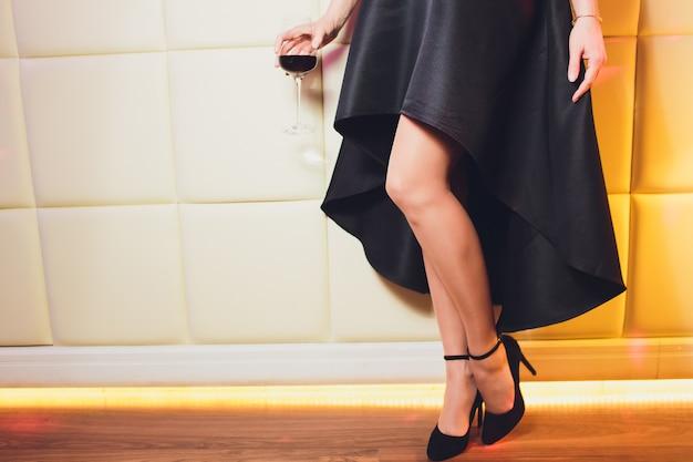 Perfekte weibliche beine, die hohe absätze und schwarzes kleid tragen. Premium Fotos