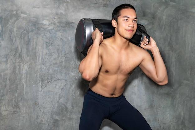 Perfektes athletisches asiatisches manntraining mit energietasche an der turnhalle. Premium Fotos