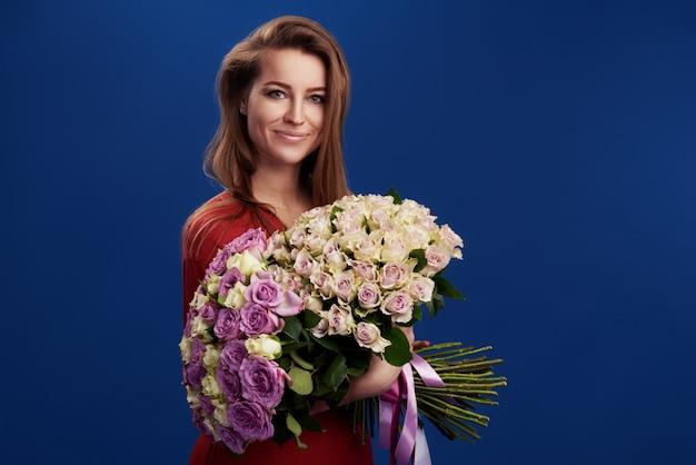Perfektes geschenk. wunderbare blumen am frauentag. zarte lächelnde brünette frau, die vor gesicht den blumenstrauß des frühlingsblumenraums für text hält Premium Fotos