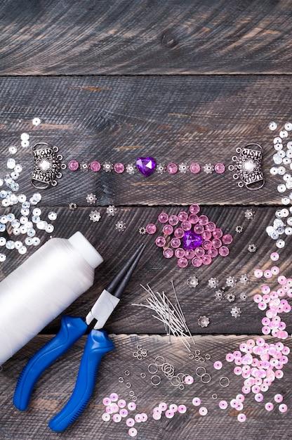 Perlen, anhänger, zange, glasherzen und accessoires, um handgemachten schmuck auf holztisch herzustellen und armband herzustellen Premium Fotos
