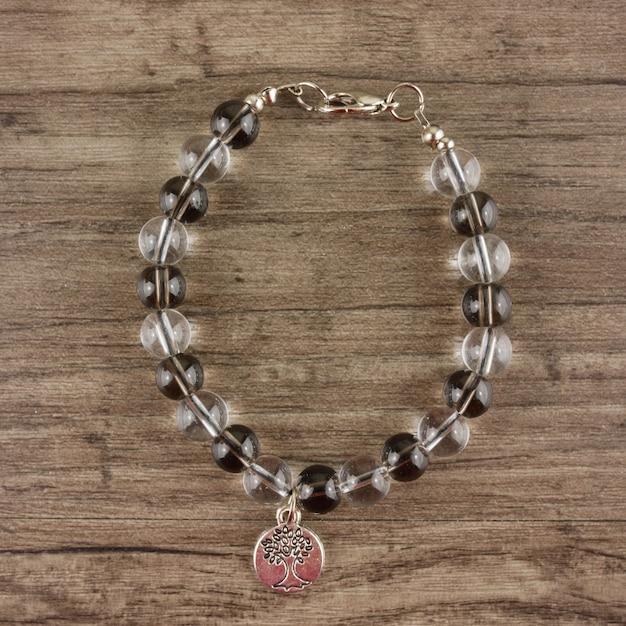 Perlen armband auf hölzernen hintergrund Premium Fotos