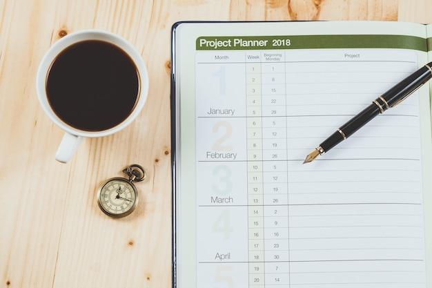 Persönlicher projektplaner mit füllfederhalter und heißem kaffee auf hölzerner tabelle. Premium Fotos
