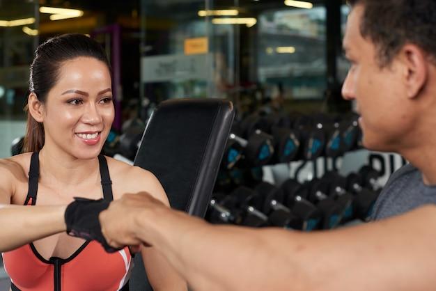 Persönlicher trainer, der einem sitzmädchen in einer turnhalle einen faustgruß gibt Kostenlose Fotos