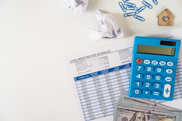 Persönliches finanzplanungskonzept. leihen sie zeitplanblatt, us-banknote, taschenrechner, ebene auf weißem hintergrund. Premium Fotos