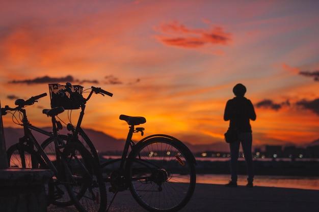 Person, die am fahrrad im sonnenuntergang steht Kostenlose Fotos