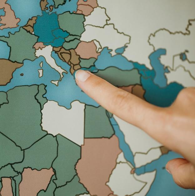 Person, die auf der karte auf europa zeigt Kostenlose Fotos