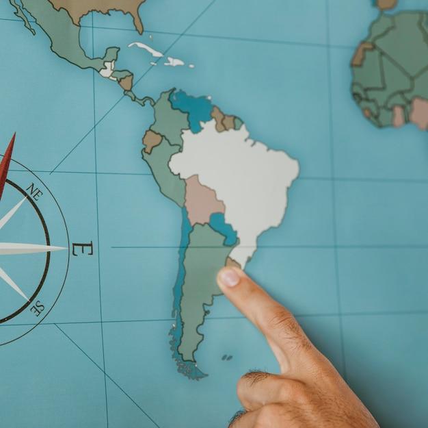 Person, die auf der karte nach südamerika zeigt Kostenlose Fotos