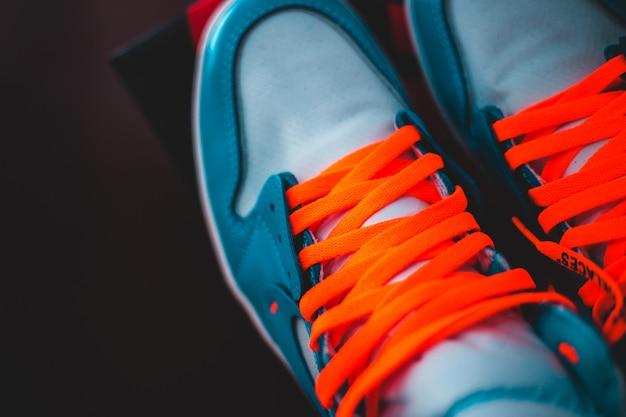 Person, die blaue und orangefarbene niedrige turnschuhe trägt Kostenlose Fotos