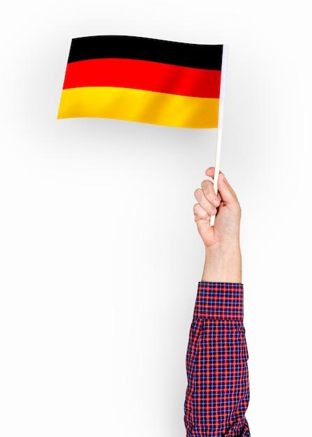 Person, die die flagge der bundesrepublik deutschland weht Kostenlose Fotos