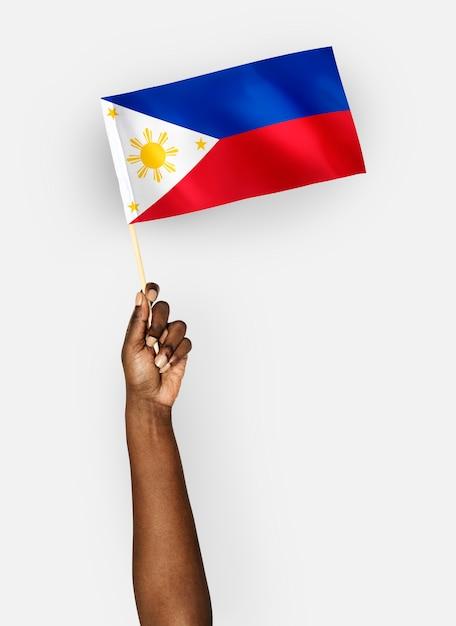 Person, die die flagge der republik der philippinen wellenartig bewegt Kostenlose Fotos