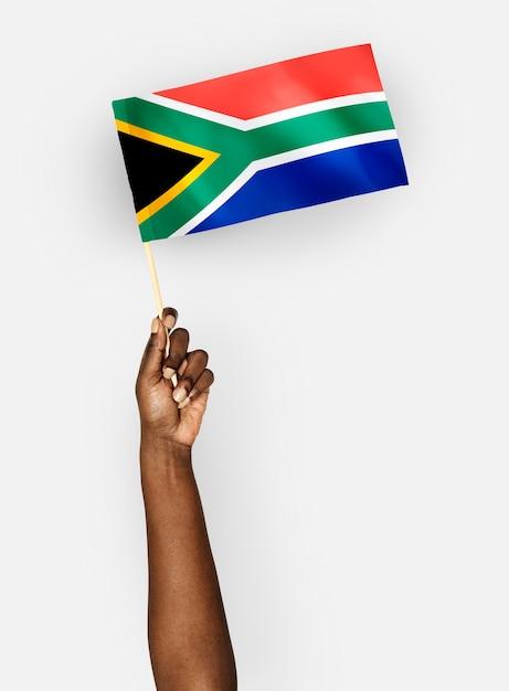 Person, die die flagge der republik von südafrika wellenartig bewegt Kostenlose Fotos