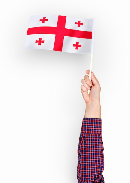 Person, die die flagge von georgia wellenartig bewegt Kostenlose Fotos