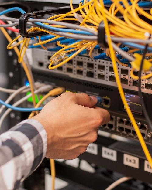 Person, die ein ethernet-kabel an einen netzwerkanschluss anschließt Kostenlose Fotos
