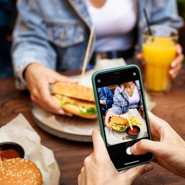 Person, die ein foto von jemandem macht, der burger isst Premium Fotos