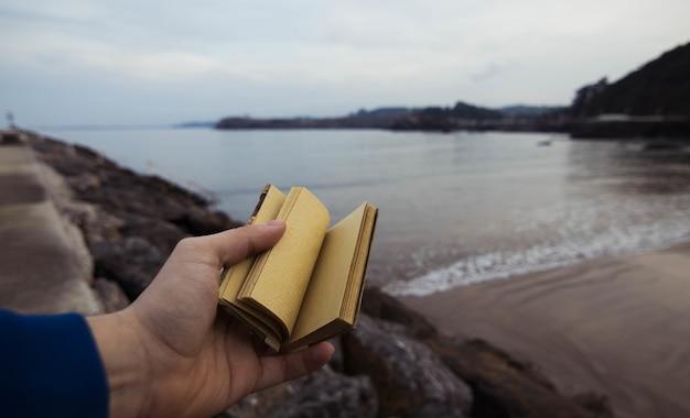 Person, die ein kleines notizbuch mit einem verschwommenen meer in candas, asturien, spanien hält Kostenlose Fotos