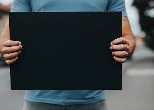 Person, die ein leeres brett zeigt, um eine bewegung zu unterstützen Premium Fotos