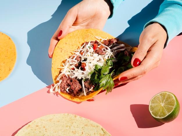 Person, die einen mexikanischen taco in der handhohen ansicht hält Kostenlose Fotos