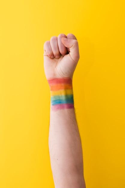 Person, die faust mit regenbogenflagge am handgelenk hält Kostenlose Fotos