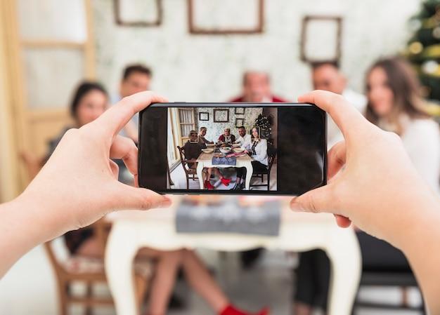 Person, die foto der familie am festlichen tisch macht Kostenlose Fotos