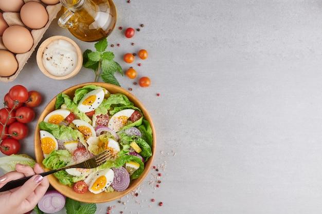 Person, die gesunden salat von frischem gemüse und gekochten eiern isst Kostenlose Fotos