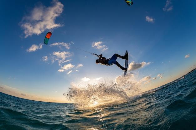 Person, die gleichzeitig beim kitesurfen surft und einen fallschirm fliegt. bonaire, karibik Kostenlose Fotos