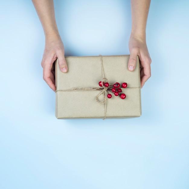 Person, die große geschenkbox mit roten beeren hält Kostenlose Fotos