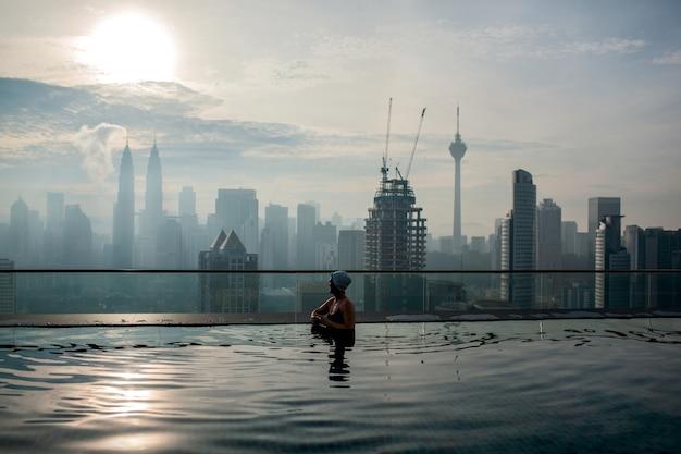 Person, die im pool entspannt und stadtpanorama genießt. kuala lumpur, malaysia Premium Fotos