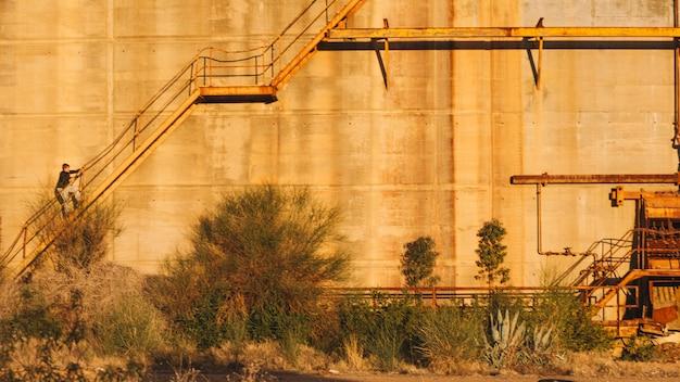 Person, die oben auf verlassenes gebäude geht Kostenlose Fotos