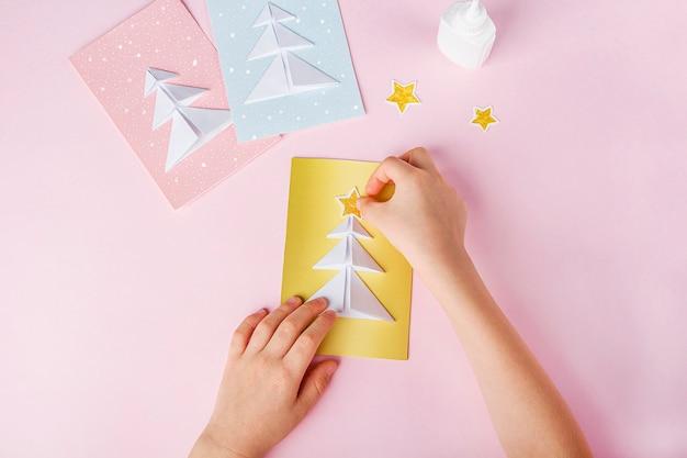 Person, die papiere klebt und karten mit weihnachtsbäumen schafft Premium Fotos