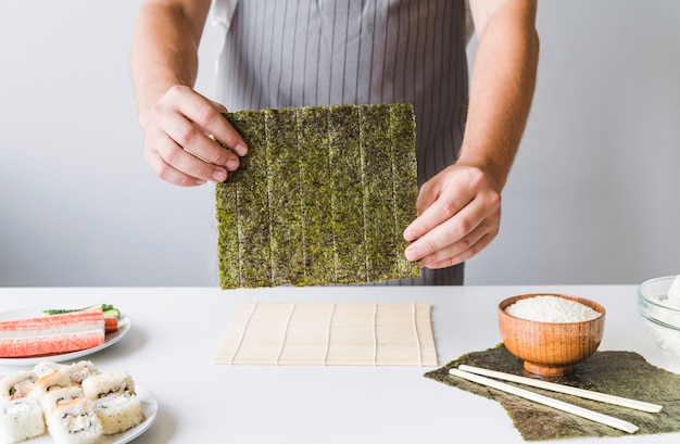 Person, die sushi nori hält Kostenlose Fotos