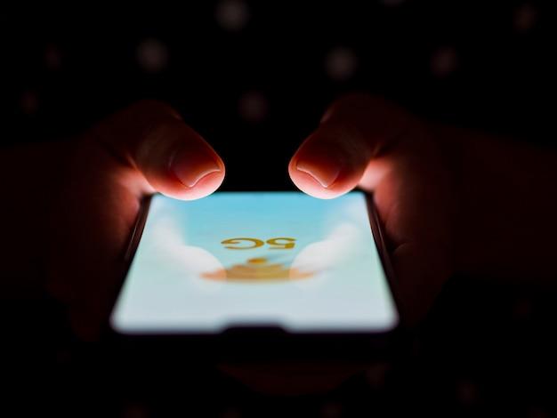 Person, die telefon im handdunkelheitshintergrund hält Kostenlose Fotos