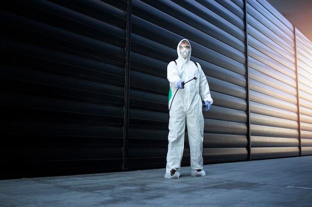 Person im weißen chemikalienschutzanzug, der desinfektion und schädlingsbekämpfung durchführt und gift sprüht, um insekten und nagetiere zu töten Kostenlose Fotos
